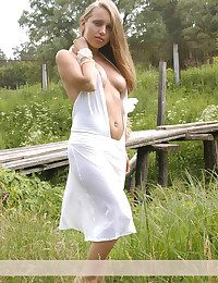 Pricha take off her milky happy rags and poses bare on a bridge at one's fingertips the country-side.
