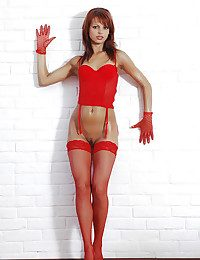 Downcast redhead with oiled body posing approximately a gloves coupled with red-hot fishnets